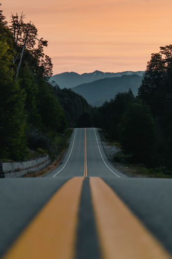 Surface level of road against sky during sunset