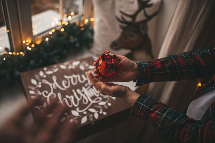 Midsection of man holding christmas decoration at home