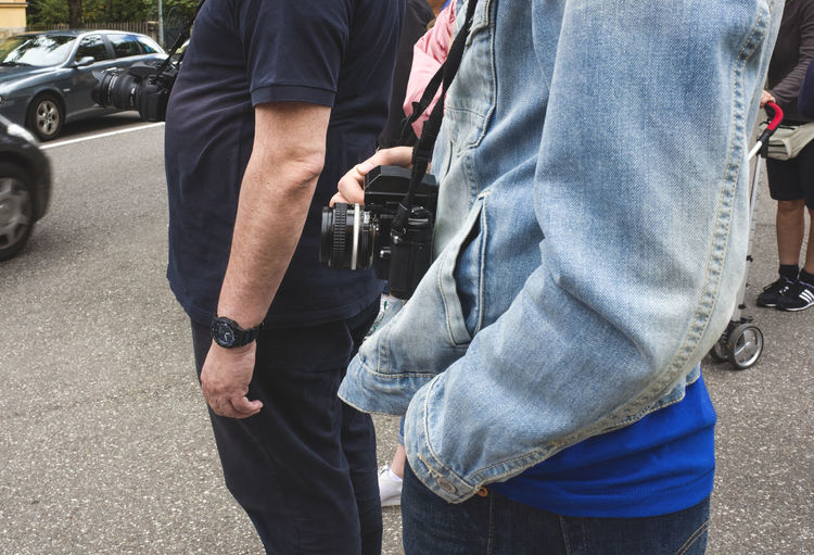 Midsection of woman with digital camera standing on street