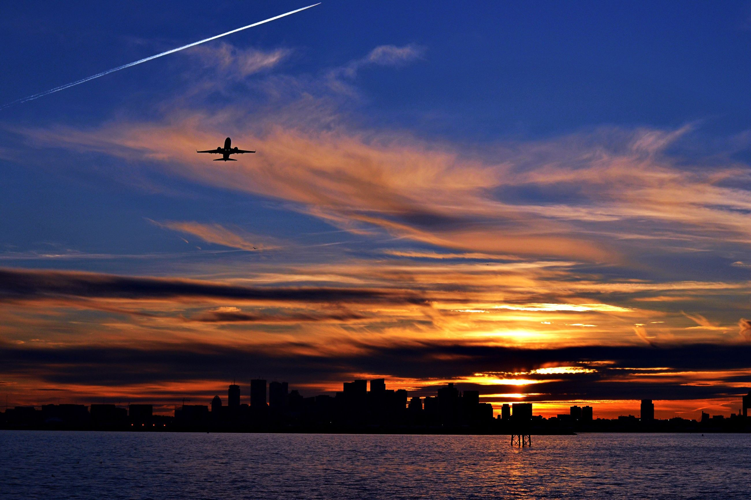 flying, sunset, airplane, sky, building exterior, night, no people, outdoors, architecture, built structure, city, low angle view, illuminated, water, skyscraper