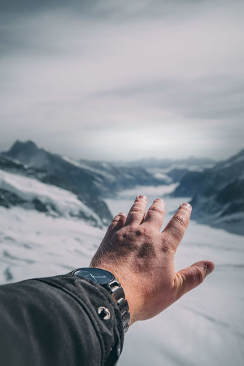 Cropped hand of man gesturing on snowcapped mountain against cloudy sky