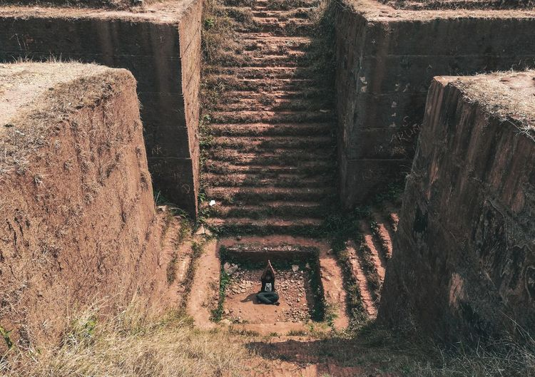 High Angle View Of Man Meditating While Sitting By Old Steps