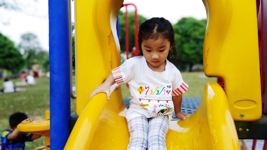 Cute girl playing on slide in playground