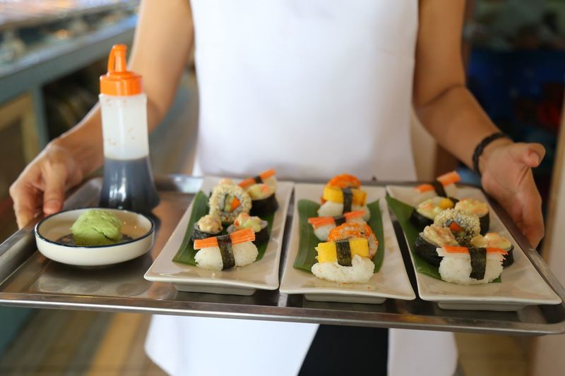 Midsection of waitress holding sushi in tray at restaurant