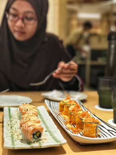 Close-up of woman having sushi in restaurant