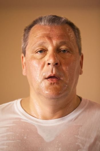 Portrait of sweaty man on beige background