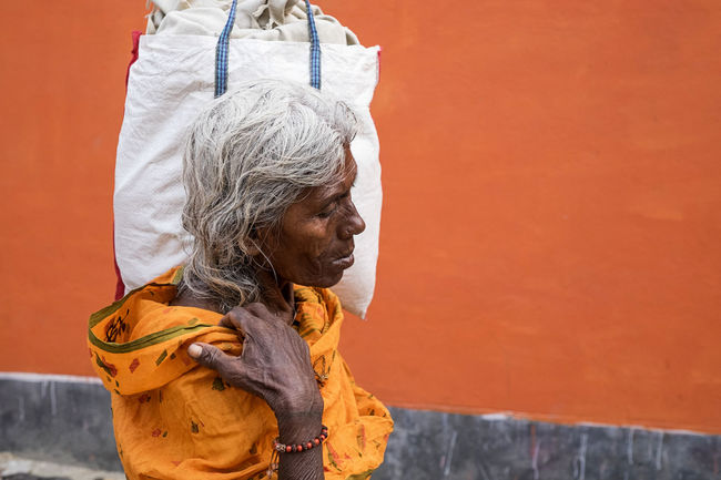 Elderly woman captured carrying a heavy load at Sonepur Mela, Bihar Carry Carrying Carrying Bag Elderly Elderly Woman Grey Hair Human Hand India Indian Woman Load Old One Person Only Women Orange Background White Hair