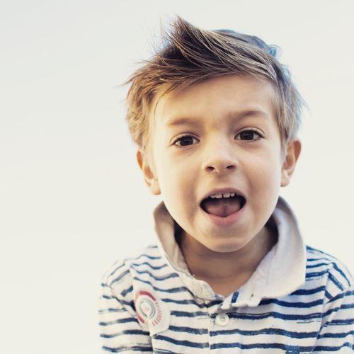 Portrait of cute boy against white background