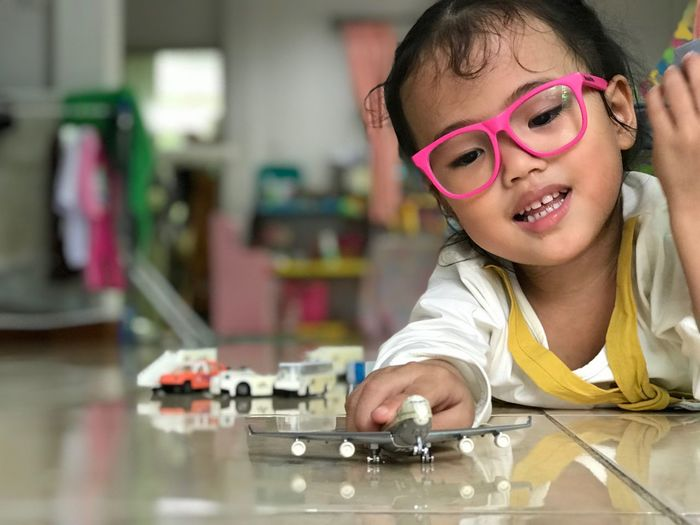 Play airplane Child Childhood Portrait One Person Indoors  Headshot Glasses Offspring Eyeglasses  Science Education Girls Real People Lifestyles Teenager Innocence Boys Front View Learning Table