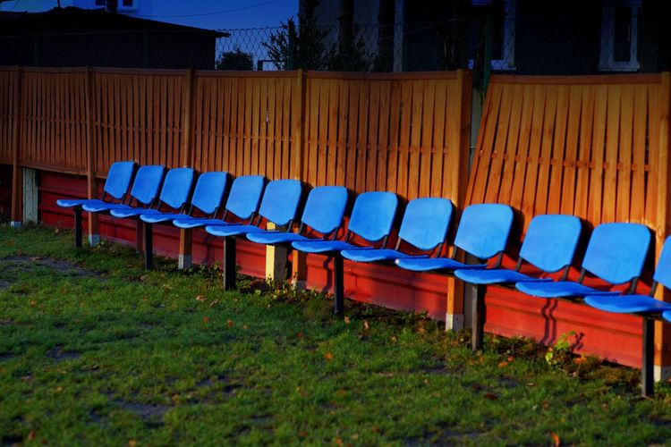 Empty chairs in row against built structures