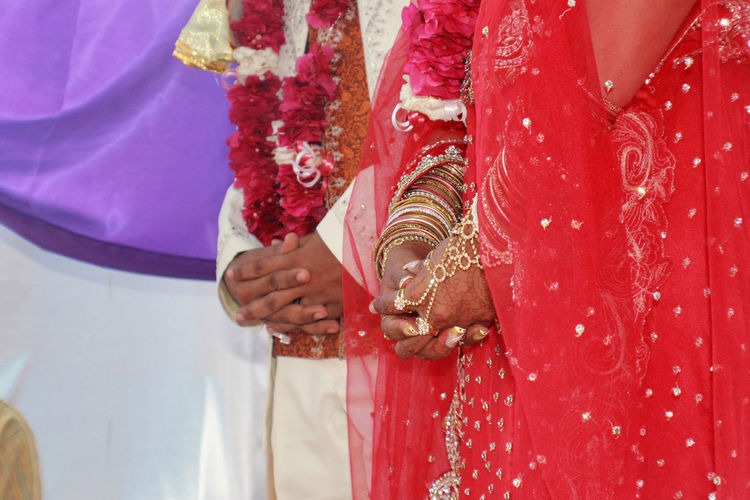 Midsection Of Bride And Groom With Hands Clasped During Ceremony