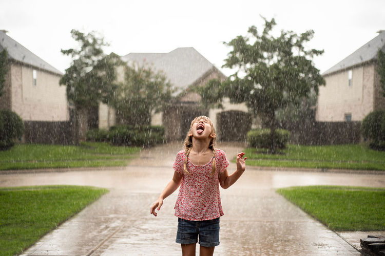 Playful girl with mouth open standing on driveway during rainfall