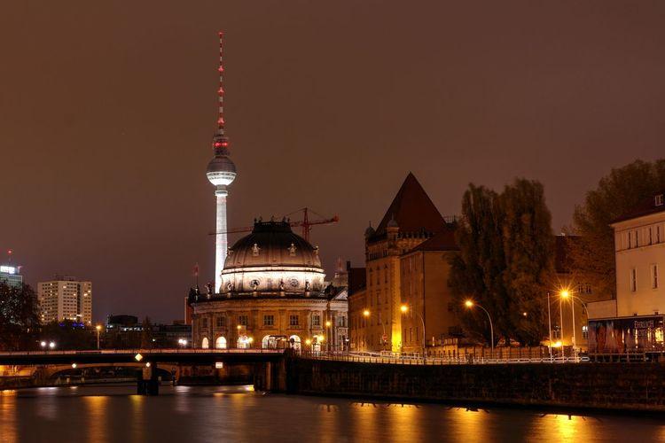 Illuminated tower bridge over river at night