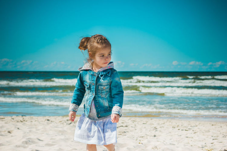 Girl standing at beach against sea and sky