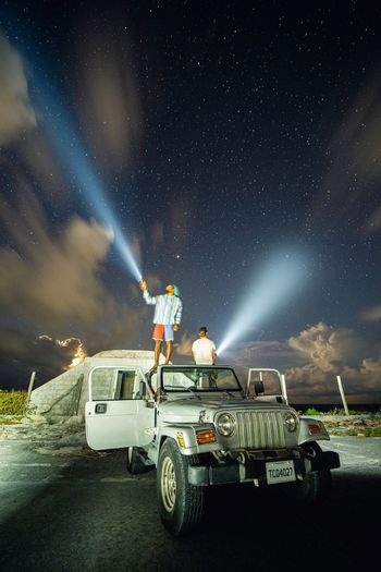 Car on illuminated road against sky at night