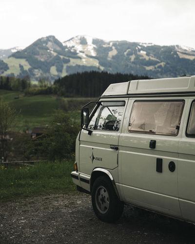 Vintage car on land against mountains