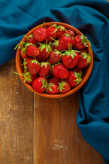 Fresh large strawberries in a clay plate on a wooden table. vertical photo