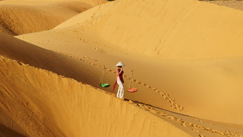 Asian woman carrying two baskets attached to a wooden stick on her shoulders in the desert at noon and heading home. Asian  Carry Carrying Culture Day Desert Desert Desert Landscape Desert Life Dunescape Hat Hot Landscape Landscapes Nature One Person Outdoors People Sand Sand Dune Sunny Day Walking Alone... Warm Work Working EyeEmNewHere Women Around The World