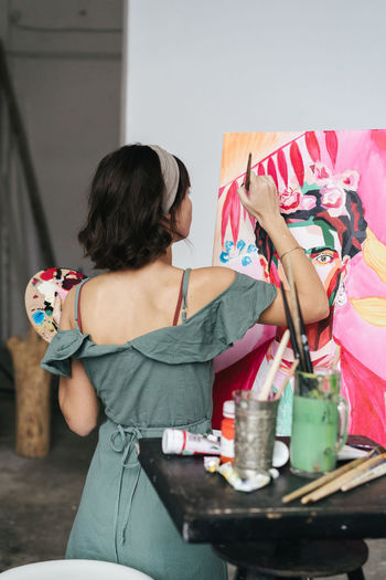 Rear view of woman painting on canvas at art studio