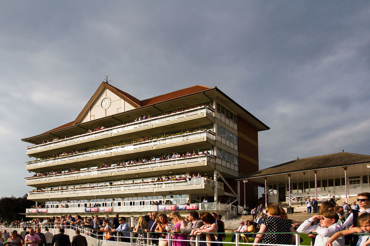 Racegoers watching horse racing at York Racecourse from the Grandstand and County Stand. Architecture Architecture Building County Stand Enjoying Life Fans Grandstand Horse Horse Racing Horse Riding Large Group Of People Outside Person Race Meet Racegoers Racing Sport Sports Structure Uk Watching Sport York York Racecourse York Races Yorkshire