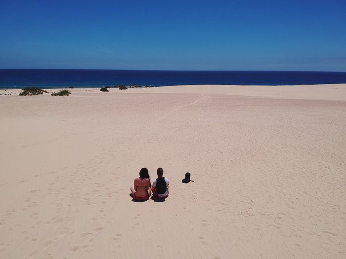 Tourist couple in Fuerteventura Drone  Dune Backpack Love Sea Desert Couple Tourist Tourism Fuerteventura Land Beach Sand Sky Sea Water Nature Clear Sky Horizon Over Water Horizon Scenics - Nature Blue Men Day Beauty In Nature Outdoors Sunny Sitting Real People Group Of People The Traveler - 2018 EyeEm Awards The Traveler - 2018 EyeEm Awards Summer Road Tripping My Best Travel Photo