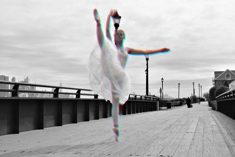 Full Length Of Woman Performing Ballet Dance On Bridge Against Sky