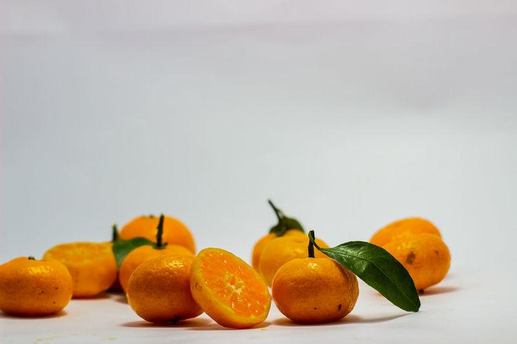 Close-up of orange fruits against white background