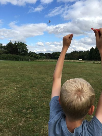 Boy with arms raised on field against sky