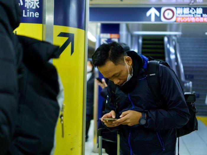 Man using phone at subway station