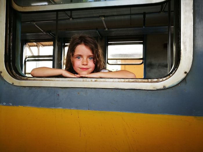Portrait Of Girl Looking Through Train's Window