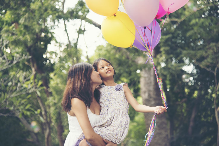 Mother carrying daughter holding balloons while standing in park