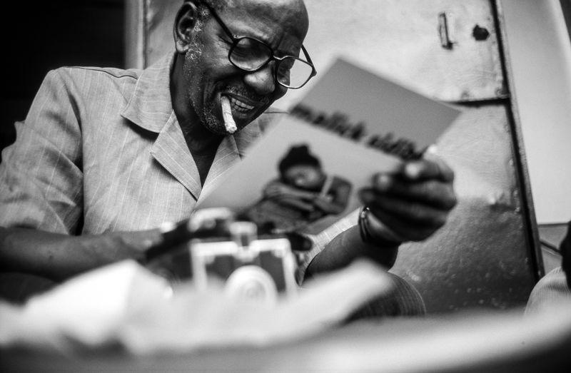 Hasselblad photo award winner Malik Sidibe 2003 in front of his photoshop in Bamako, Mali AWARD Died: April 14, 2016, Bamako, Mali Documentary Photography Hommage MALICK SIDIBÉ RETROSPECTIVE MALI TWIST IN PARIS Oct 20, 2017 - Feb 28, 2018 Malian Photographer Malik Sidibe The Week On EyeEm African Photography Hasselblad Monochrome Paris Photography Photographer Photography Portrait Of A Photographer Portrait Photography Reportage Winner Mali Twist