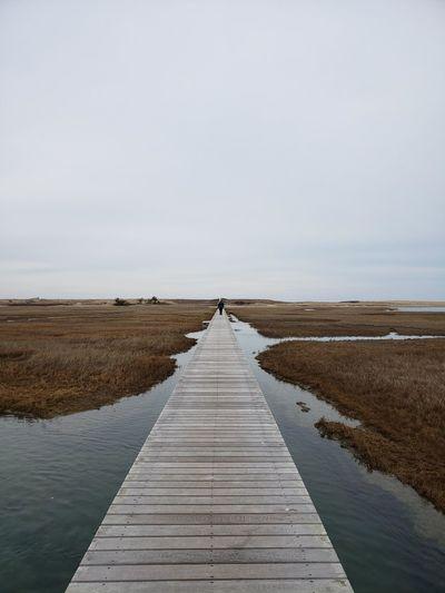 Boardwalk leading towards pier against sky