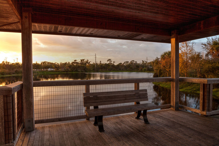 Sunset Wooden bench on a secluded, tranquil boardwalk along a marsh pond in Freedom Park in Naples, Florida Bench Freedom Park Marsh Nature Panorama Panoramic View Pond Reflection Tranquility Waiting Wetland Benches Boardwalk Clouds And Sky Florida Landscape Seat Sunset Water