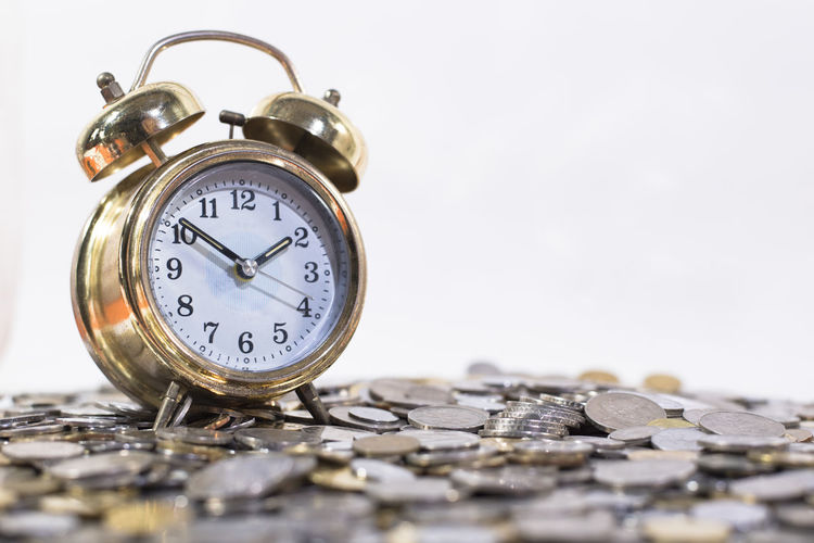 Close-up of alarm clock with coins against white background