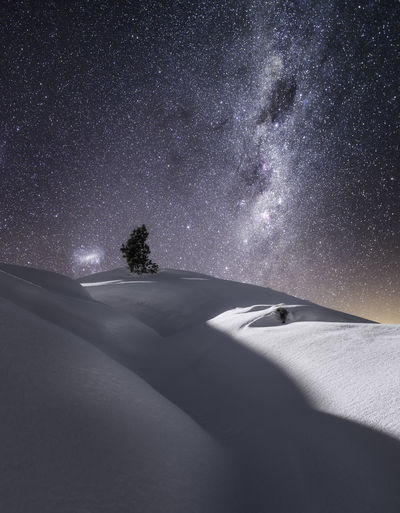 Scenic view snow covered hills against star field at night