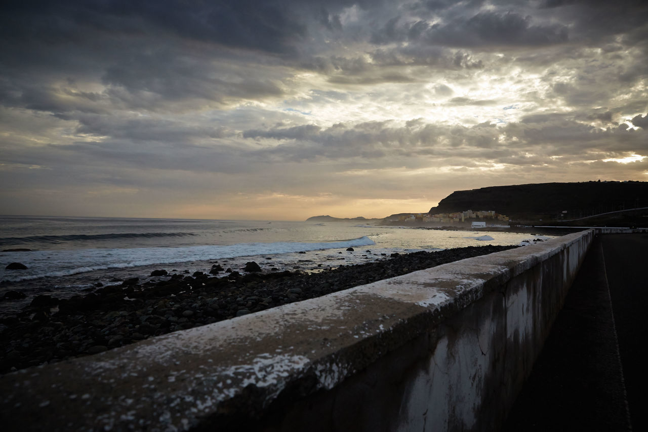 Retaining Wall By Sea Against Cloudy Sky During Sunset