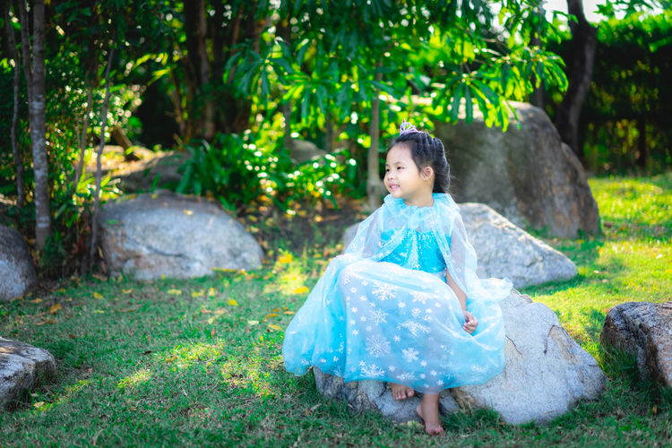 Full length of cute girl wearing dress sitting on rock in park