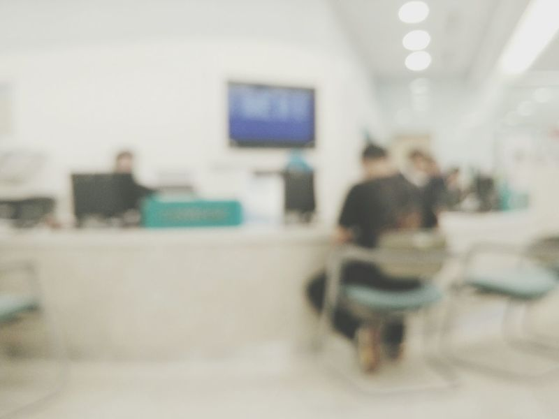 Men Sitting Person Rear View Indoors  Casual Clothing Focus On Foreground Selective Focus Blurred Day Cashier  Counter Over The Counter Lobby Corperates Company Defocused Background Waiting Bokeh Manual Focus Defocus Hospital Time Hospital Illuminated Surface Level