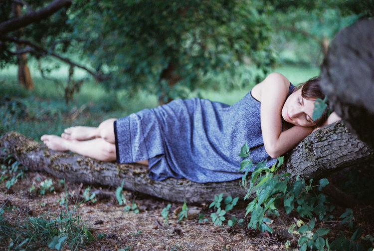 Woman sleeping on log in forest