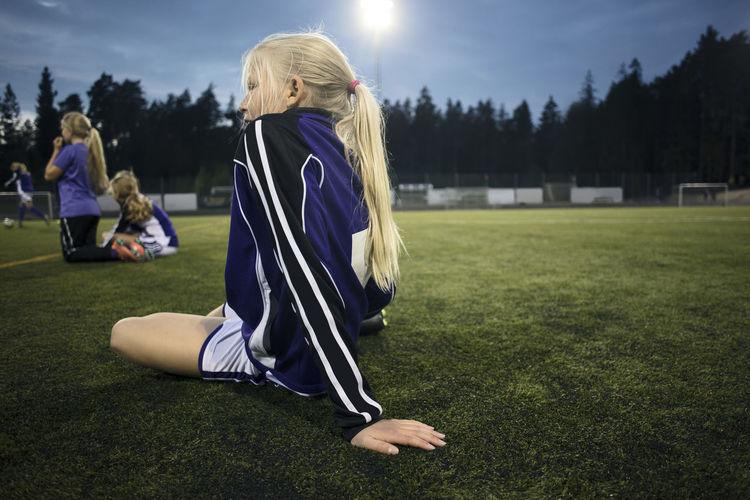 Rear view of women sitting on field