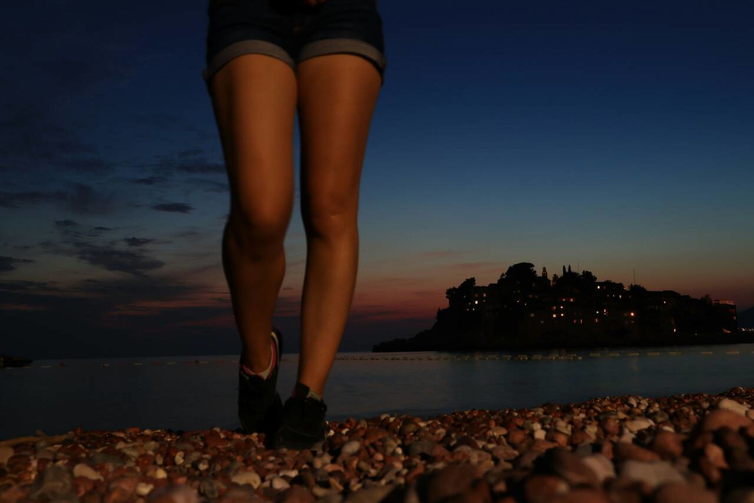 sky, one person, water, real people, human leg, lifestyles, low section, body part, human body part, nature, standing, adult, women, solid, rock, sunset, beach, leisure activity, pebble, human limb