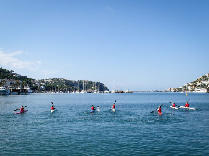 Rear View Of Children Canoeing In Sea Against Clear Blue Sky