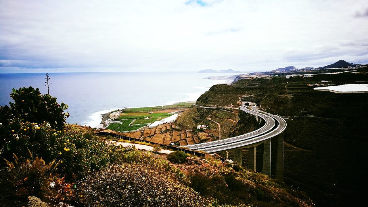 sea, high angle view, beauty in nature, sky, nature, scenics, winding road, water, landscape, mountain, tranquil scene, no people, tranquility, road, outdoors, transportation, horizon over water, day, cliff, curve, mountain road, tree, grass
