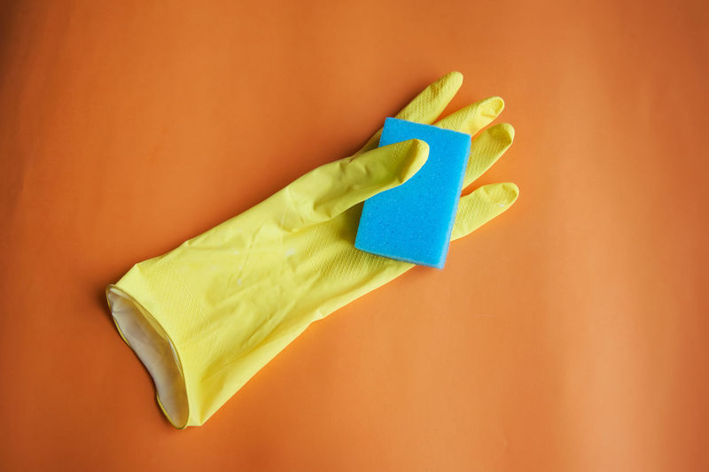 High Angle View Of Glove And Sponge On Table
