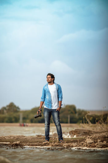 Full length portrait of young man standing on land
