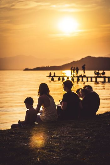 Family in the sunset Sunset Outdoors Sitting People Beauty In Nature Nature Water Togetherness Gardasee Largo Di Garda Family Beautiful Italy🇮🇹 EyeEmNewHere The Great Outdoors - 2017 EyeEm Awards Live For The Story Connected By Travel