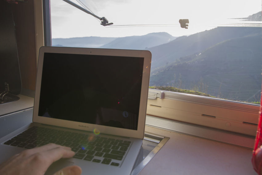 Working on laptop with beautiful view through window of vehicle/motorhome Mobile Office View Working Beautiful View Laptop Mountains Window