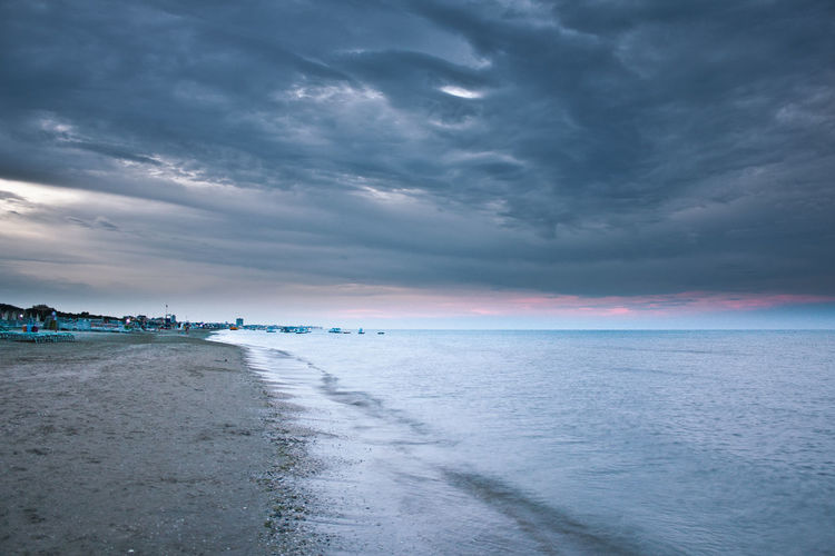 Scenic view of calm sea against cloudy sky