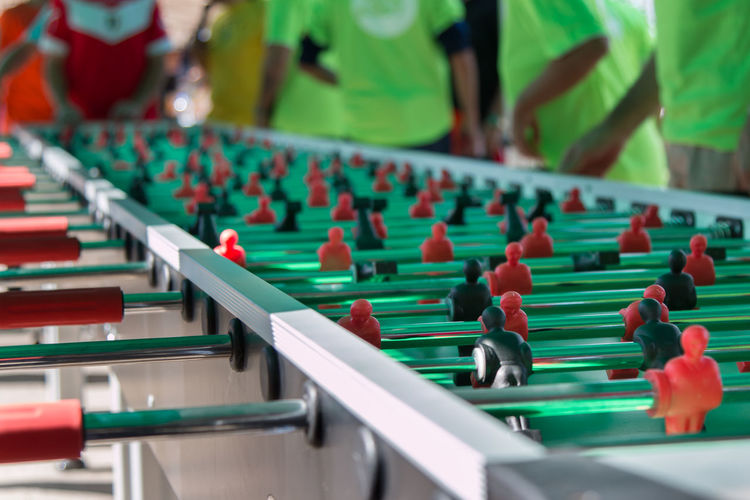 Midsection of friends playing foosball